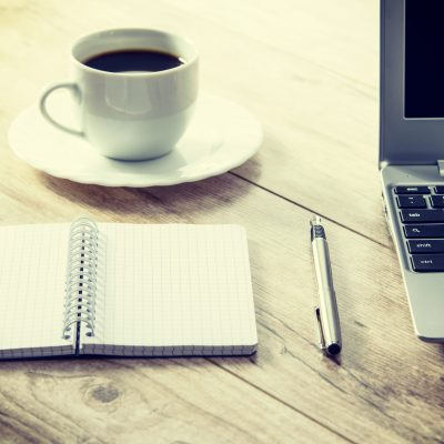 Blank notepad and a pen next to a laptop and coffee on a wooden vintage desk